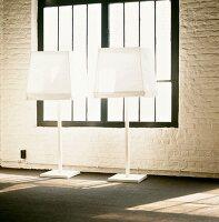 Schwarzgerahmtes, altes Fabrikfenster und geweisselte Ziegelwand hinter weissen Stehlampen