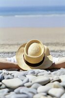 Man in hat lying on beach