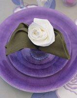 Place-setting with napkin folded into rose shape