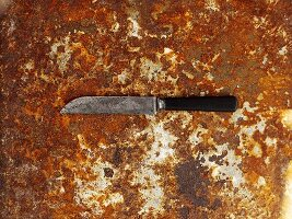 A knife on a rusty baking tray, seen from above