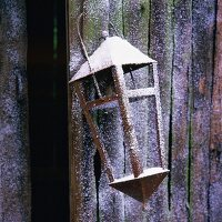 Lantern hanging on wooden wall
