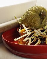 A red bowl with decorative Oriental characters, jackfruit and flowers