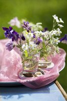 Meadow flowers in glasses and shells on tray