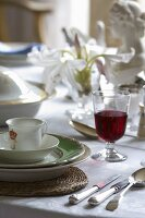 A table laid with elegant porcelain, wine glasses and cutlery