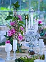 Laid table with pyramid of flowers and candlesticks