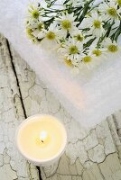 Burning candle and towel with white asters