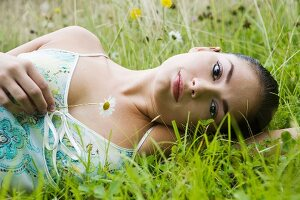 Young woman lying in flowery meadow