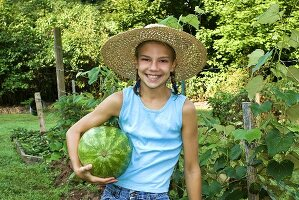 Young Girl Holding Watermelon in Garden
