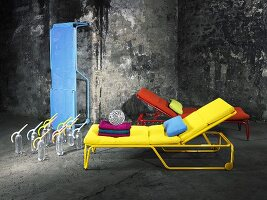 Coloured loungers arranged in front of a weathered, grey stone wall