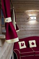A comfortable red corner sofa in a rustic hut