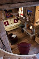 Looking down onto a room in a hut with a fireplace