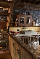 A view into a kitchen of a rustic house with a stone sink