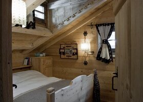 A bedroom under the roof of a wooden hut
