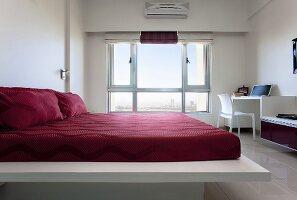 A bed with red bed clothes in a white room with a large window
