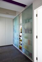 A built-in cupboard full of glasses with sliding doors made of blue grass