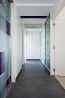 A hallway in an apartment with built-in cupbaords and a dark floor