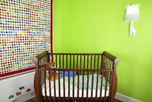 Crib in the corner of a child's room in front of a vibrant green wall