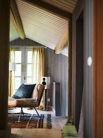 View through an open door into a wood paneled attic in a country home at a chair and French window