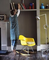 A plastic rocking chair, a floor lamp on wheels and a woman in front of a bookshelf