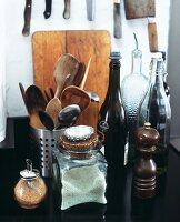 A pepper mill, a jar of salt, brown sugar in a shaker, wooden spoons etc