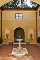 A fountain in the courtyard of a Mediterranean villa with a terracotta floor and a yellow facade