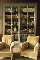 Old fashioned plush armchairs and a cabinet