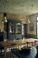 A rustic dining room with a straw ceiling and a dark grey cabinet in front of a brick wall