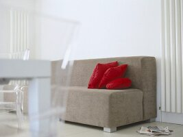 Sitting room with neural coloured sofa with red cushions and painted floorboards.