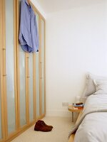 Bedroom with fitted wardrobe with wooden framed doors.