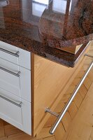 Central island unit with granite worktop in contemporary kitchen