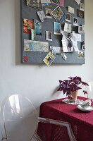 Louis Ghost chair next to table beneath pinboard