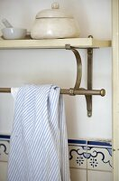 Tea towel over steel bar fixed below shelf