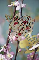 A wooden rabbit decoration hanging from flowering twigs