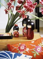 A detail of Japanese styled sitting room, wooden painted dolls, embroidered cushion, pink flowers,