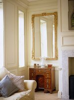 Sitting room with white panelled walls and gilt mirror above antique knee hole desk.