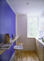 A detail of a modern kitchen with breakfast bar, blue feature wall, sink unit, wooden flooring,