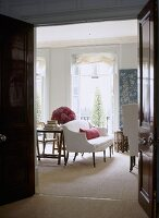 A view through an open door into a traditional sitting room, upholstered sofa, French windows