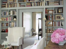 A traditional sitting room with built in shelves, upholstered wing back armchair, open doorway to bedroom