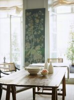 A traditional dining room, rustic, country wooden table, chairs, white tableware