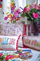 A tea break on a bed with colourful cushions and a bunch of flowers