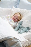 Little girl lying in bed with her plush animals