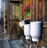 Three milk cans on the wall of a wooden house
