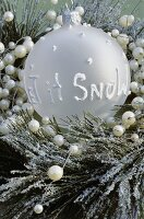 Winter arrangement, bauble with the words Let it snow
