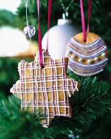 Gingerbread cookies decorated with coloured icing and silver pearls hanging on a Christmas tree