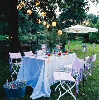 A festively laid table in a garden decorated with flowers, lanterns, lantern garlands and torches