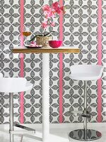 A white bar table with two bar stools against patterned wallpaper