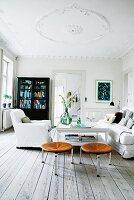 Weisses Wohnzimmer mit schwarzem Schrank, Hussensessel und Lederhocker