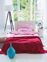 Single bed with Japanese-style linen, floor lamp and bedside table