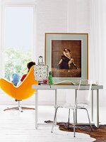 Desk, plexiglas chair and photo of sumo wrestlers in wooden frame