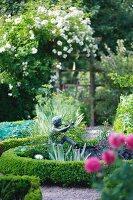 A sculpture of a flute player in a summery garden